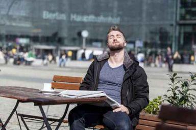 Attraktiver Mann sitzt in einem Cafe und geniesst die Sonnenstra